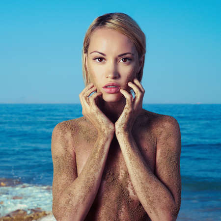 nude nature: Elegant blonde with body in sand of sea