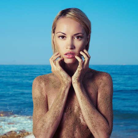 nude female body model: Elegant blonde with body in sand of sea
