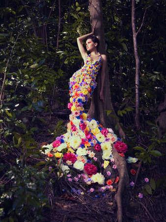 Bloeiende prachtige dame in een jurk van bloemen in het regenwoud