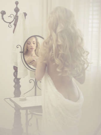 sexy elegant blonde woman in front of the mirror