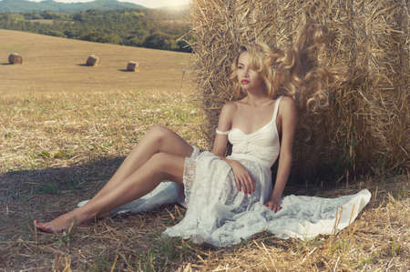 Photo of blonde in a field with haystacks