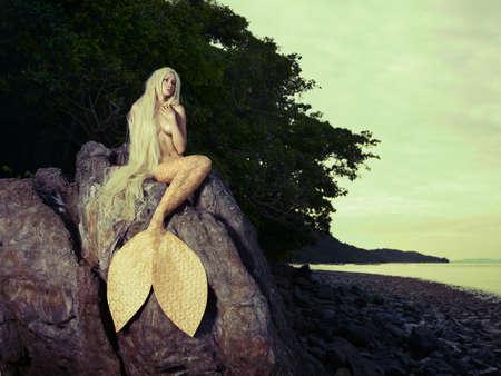 Sch?ne modische Meerjungfrau sitzt auf einem Felsen am Meer