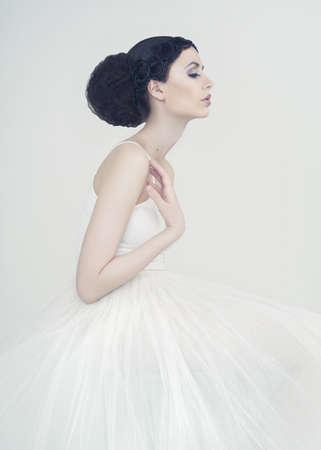 白い背景の上の美しいエレガントなバレリーナの肖像画