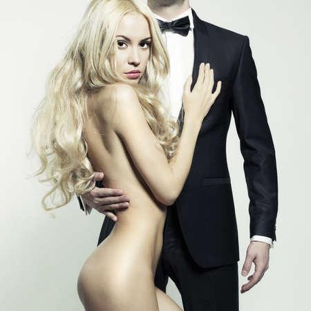 Modische Foto der schönen nackten Frau und Mann im Anzug
