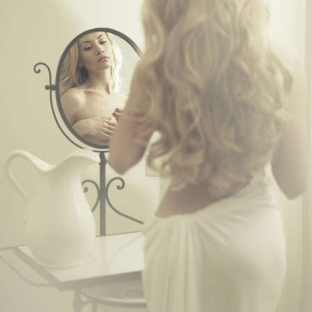 elegant blonde woman in front of the mirror