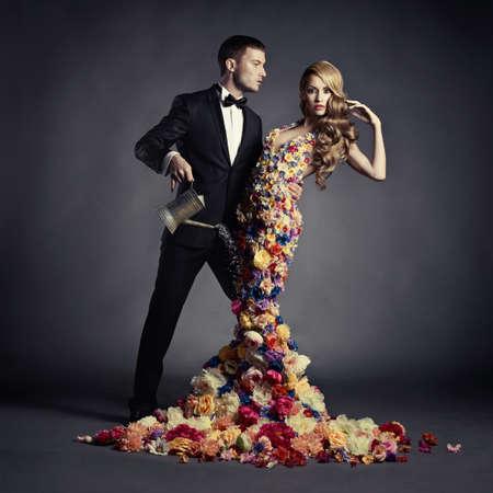 花のドレスで美しい女性の水まき缶から若い男が注ぐ
