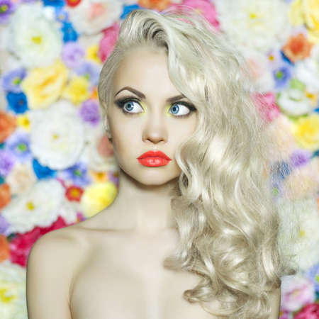 Fashion portrait of beautiful blonde on flower background