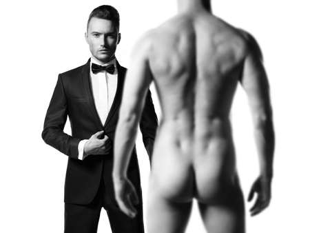 desnudo masculino: Hombre elegante en traje negro delante de modelo masculino atl�tico desnudo Foto de archivo