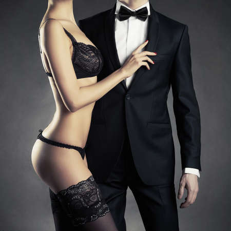 Art photo of a young couple in sensual lingerie and a tuxedo 스톡 콘텐츠