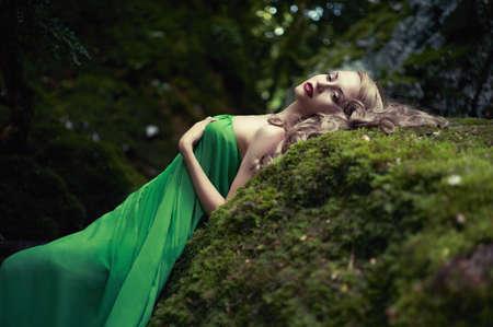 labios sensuales: Retrato de la mujer elegante con el pelo de lujo en un bosque de coníferas