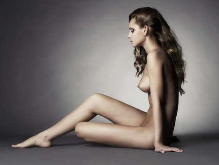 Nackte elegante Sitz Dame auf grauem Hintergrund Standard-Bild - 29582172