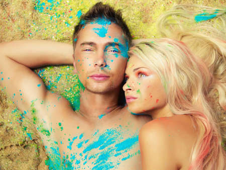 Romantic couple painted colored powders on the sand. Holi festival, India Stock Photo - 30020361