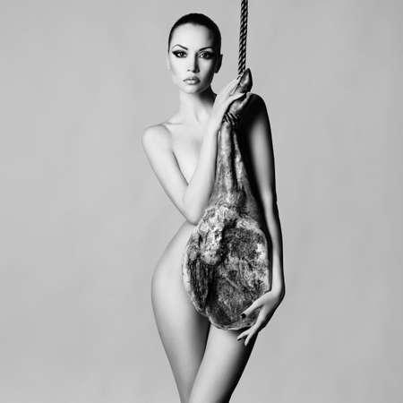 nude young woman: Stylish art photo of nude elegant woman with Iberian jamon
