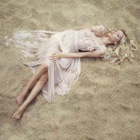 Fashion art portrait of beautiful woman on sand photo