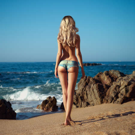 Beautiful slender blonde on sea. Summer travel photos photo