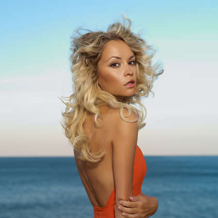 Beautiful young blond woman outdoors portrait at the sea photo