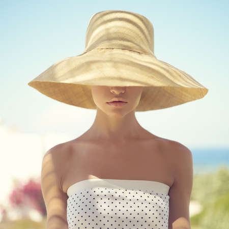 Mooie jonge dame in strooien hoed in het zonlicht Stockfoto
