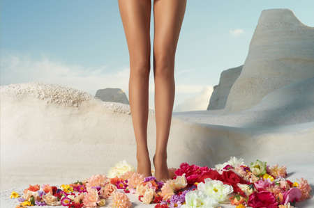 long sexy legs: Beautiful girl with perfect legs standing in the flowers Stock Photo