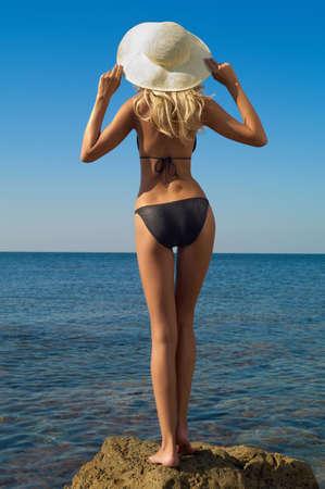 Beautiful slender blonde on sea. Summer travel photos photo