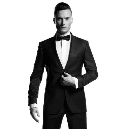 Portrait of handsome stylish man in elegant black suit photo