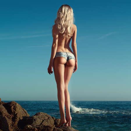 nue plage: Belle blonde élancée sur la mer. Photos de voyage d'été