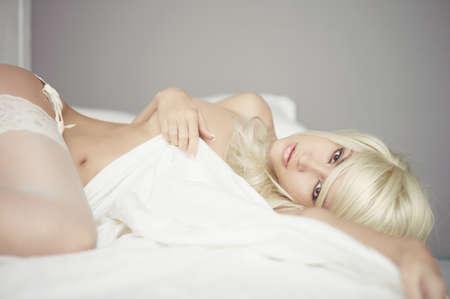 desnudo: Retrato de moda de mujer elegante joven en la cama