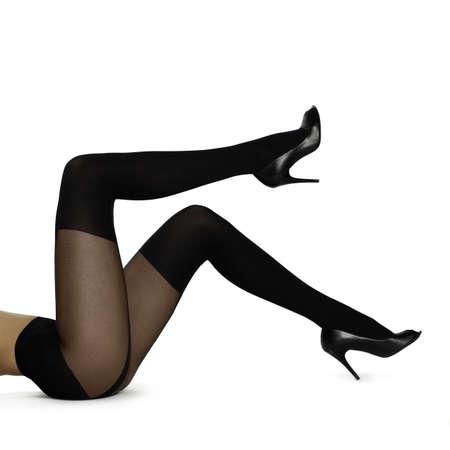 Slanke vrouwelijke benen in kousen op wit wordt geïsoleerd. Conceptuele mode art photo Stockfoto