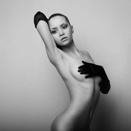 chica desnuda: elegante chica desnuda con los guantes. Estudio de foto de moda. Foto de archivo