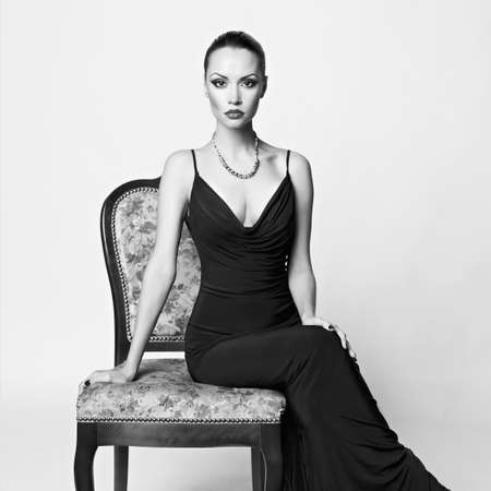 Black and white portrait of beautiful lady in luxury armchair