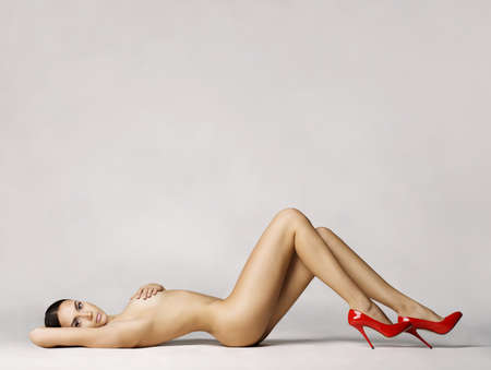 nude women: elegant naked woman in red shoes laying on white background Stock Photo