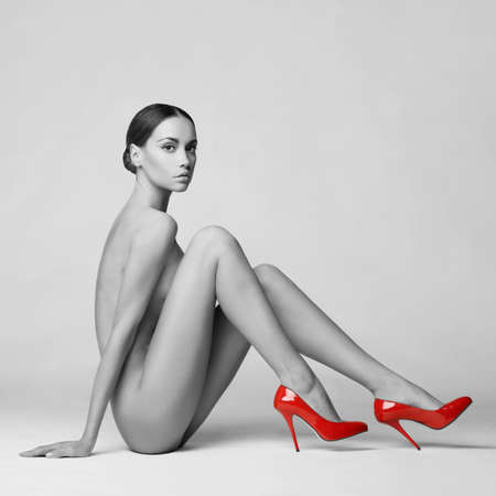 beautiful nude lady with perfect body sits in red shoes. Conceptual fashion art photo Stock Photo