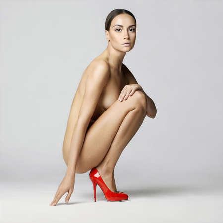 modelo desnuda: hermosa dama desnuda con el cuerpo perfecto se sienta en los zapatos rojos. Moda conceptual de arte fotográfico