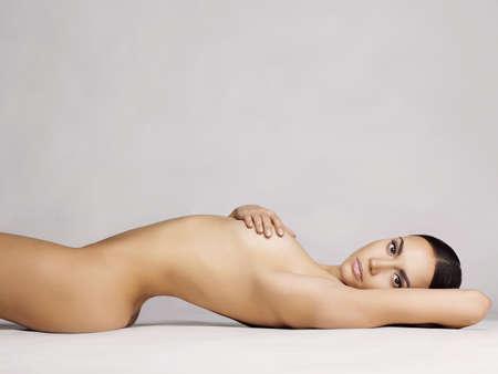 studio photo of elegant naked lady laying on white background