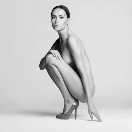 nude: beautiful nude lady with perfect body sits in red shoes. Conceptual fashion art photo Stock Photo