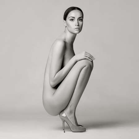 nude female buttocks: beautiful nude lady with perfect body sits in red shoes. Conceptual fashion art photo Stock Photo
