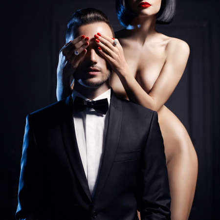 Fashion studio photo of a sensual couple on black background