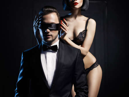 nude women: Fashion studio photo of a sensual couple in lingerie and a tuxedo