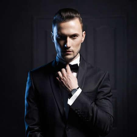 traje: Retrato de hombre guapo elegante en traje negro elegante