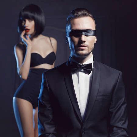 ランジェリーとはタキシードで官能的なカップルのファッションのスタジオの写真