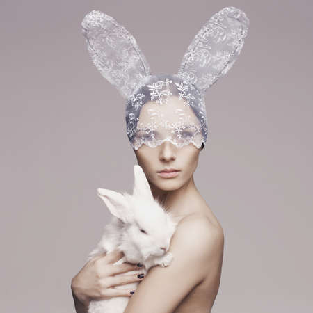 Studio fashion portrait of beautiful lady with white rabbit Stock Photo