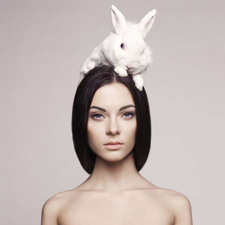 head of animal: Studio fashion portrait of beautiful lady with white rabbit Stock Photo