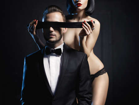 woman sex: Fashion studio photo of a sensual couple in lingerie and a tuxedo