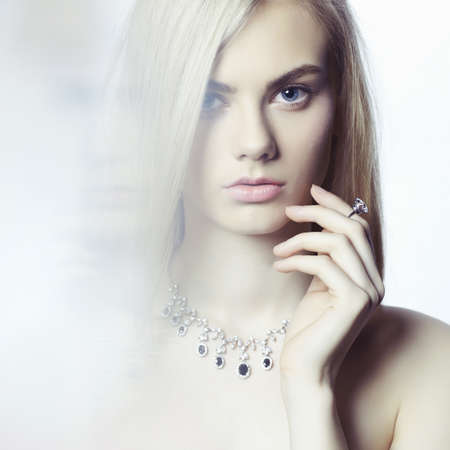 Studio fashion portrait of young beautiful lady in jewelry 스톡 콘텐츠