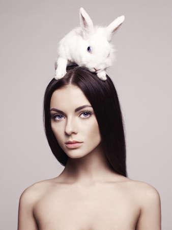 animal sexy: Studio fashion portrait of beautiful lady with white rabbit Stock Photo