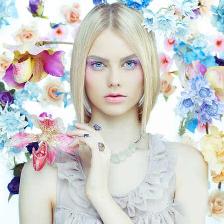 Fashion art portret van mooie dame in delicate bloemen rond