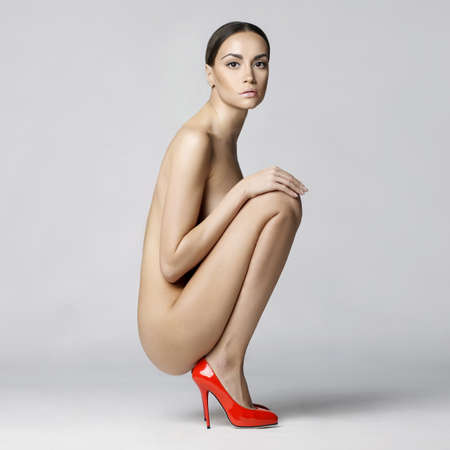 nude art model: beautiful nude lady with perfect body sits in red shoes. Conceptual fashion art photo Stock Photo