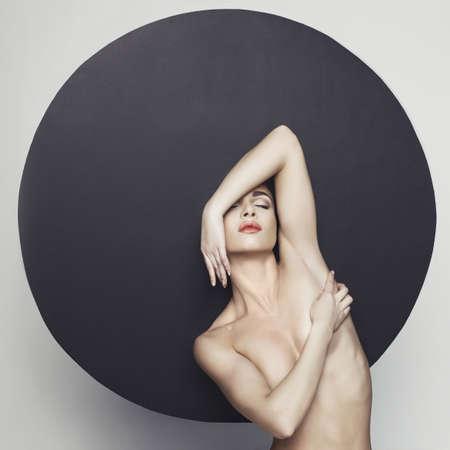 Fashion studio foto van naakt elegante dame in grote zwarte hoed. Gezondheid en schoonheid