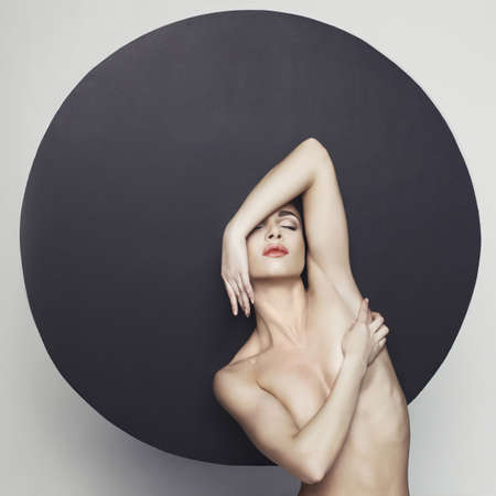 Fashion studio photo of nude elegant lady in giant black hat. Health and beauty