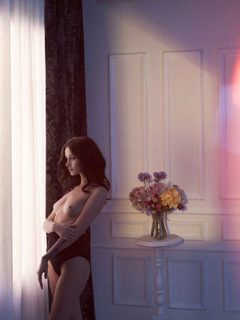 brunette naked: Fashion art photo of sensual lady with flowers. Home interior. Morning