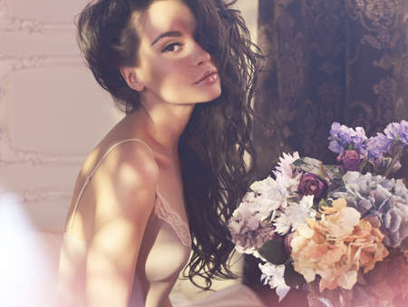 Fashion art photo of beautiful lady with flowers. Home interior. Morning